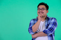 Happy young overweight Asian hipster man thinking