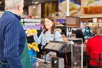 Kassierer und Kundin an der Supermarkt Kasse