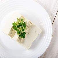 Flat lay view at Soy Bean curd tofu on clay dish closeup. Non-dairy alternative substitute for cheese