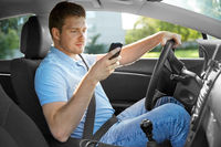 man driving car and using smartphone