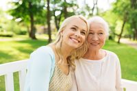 daughter with senior mother sitting on park bench