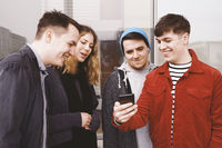 young man showing something funny on his smartphone to a group of teenage friends