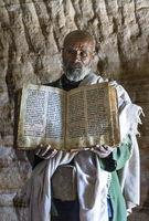 Orthodoxer Priester der Felsenkirche Mikael Mellehayzengi zeigt ein auf Pergament in der Kirchensprache Ge'ez handgeschriebenes Buch Wunder der Maria