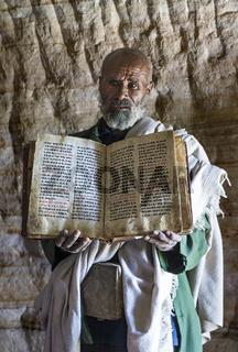 Orthodoxer Priester der Felsenkirche Mikael Mellehayzengi mit Buch Wunder der Maria,Äthiopien