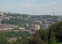 a panoramic view of sowerby bridge in west yorkshire with streets and houses surrounded by trees and wainhouse tower in the distance
