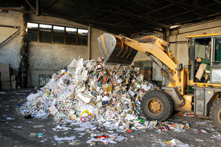 Excavator dumps cardboard garbage at waste recycling plant
