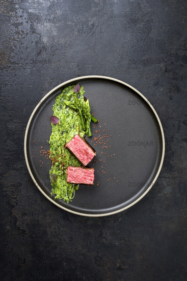 Blanched green asparagus tips with barbecue dry aged wagyu fillet steak and avocado coriander relish as top view on a modern design plate with copy space