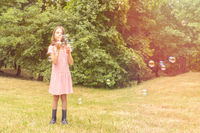 Girl playing with bubbles in a public park