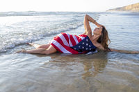 A Lovely Brunette Model Poses Nude At The Coast With An American Flag