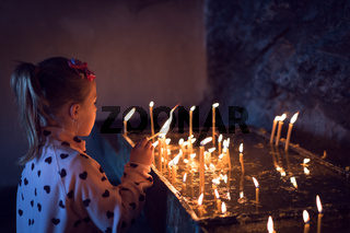 Little caucasian girl lightening the memorial candles
