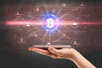 Hand using phone with bitcoin link network and online concept