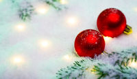 Rote Weihnachtskugeln im Schnee mit magischen Lichtern