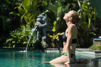 Sensual young woman relaxing in outdoor spa infinity swimming pool surrounded with lush tropical greenery of Ubud, Bali.