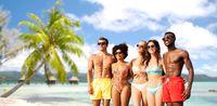 happy friends in swimwear hugging on summer beach