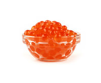 Close up glass bowl of red salmon caviar on white