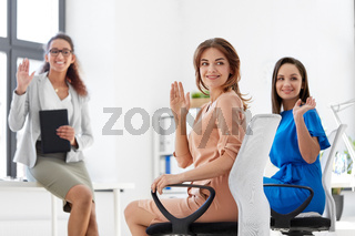 businesswomen waving hands at meeting in office