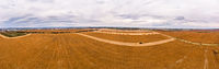 Aerial drone view of farmland. Combines work in the agricultural lands, harvesting. 180 degrees panoramic landscape