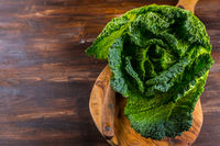 Fresh raw savoy cabbage with garlic and knife on wooden background