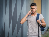 Young man standing outdoors talking on cellphone