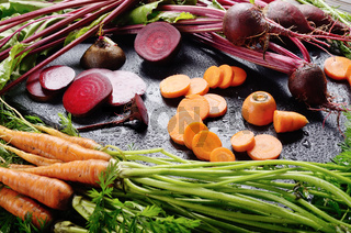 Vegetable background of beets and carrots on kitchen table close up view