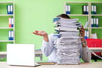 The businessman having problems with paperwork and workload