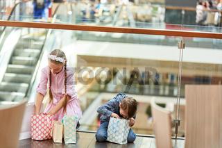 Zwei Kinder schauen in ihre Einkaufstüten