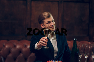 Very handsome man in a suit raises the glass of champagne