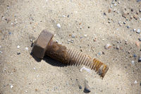 rostige Schraube am Sandstrand