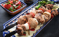 Traditional Greek souvlaki barbecue skewer  tomato onion salad and paprika as closeup on a plate