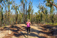 Woman running along dirt trail in forest area