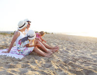 Laughing family with father, mother, daughters having picnic at the beach