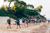 Group of backpackers walking on a sandy road along the sea shore