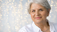 portrait of senior woman over festive lights