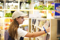 Teen girl choosing the book in book store, education concept