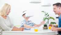 Happy caucasian family at home at dinning table, having fun playing games using virtual reality headset