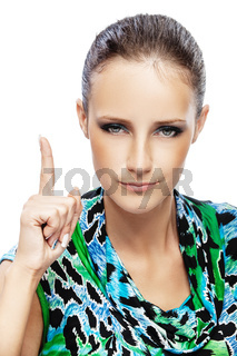 beautiful woman with dark hair in verdant motley dress lifts finger up