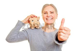 Seniorin mit Sparschwein hält Daumen hoch