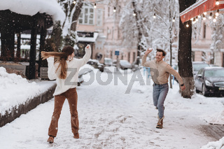 Joyful young couple in sweaters is playing snowballs at the street.