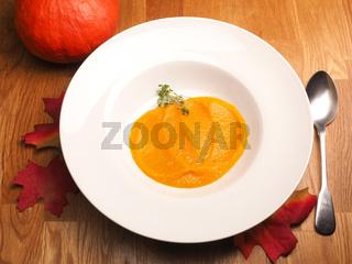 Creamy organic pumpkin soup on a white plate