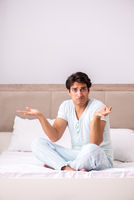 Young man doing yoga in bed