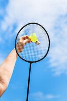 female hand hits shuttlecock by badminton racquet