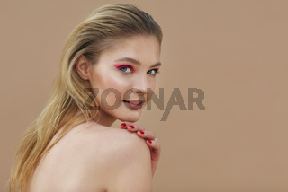 Beautiful model girl with red manicure on nails with bright make up and cosmetics