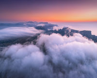 Aerial view of low clouds, mountains, sea and colorful sky at sunset.