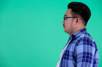 Profile view of young overweight Asian hipster man