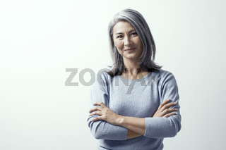 Beautiful woman with gray hair standing near the wall hands crossed