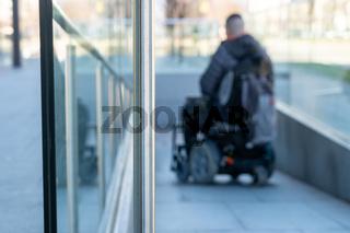 Man in a electric wheelchair using a ramp in blur
