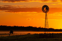 Silhouette of windmill on farmland against orange yellow sky