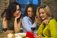 Female friends toasting with red wine in the kitchen and looking at mobile phone