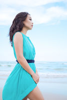 Young beautiful asian woman is walking along the tropical sea beach