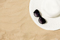 straw hat and sunglasses on beach sand